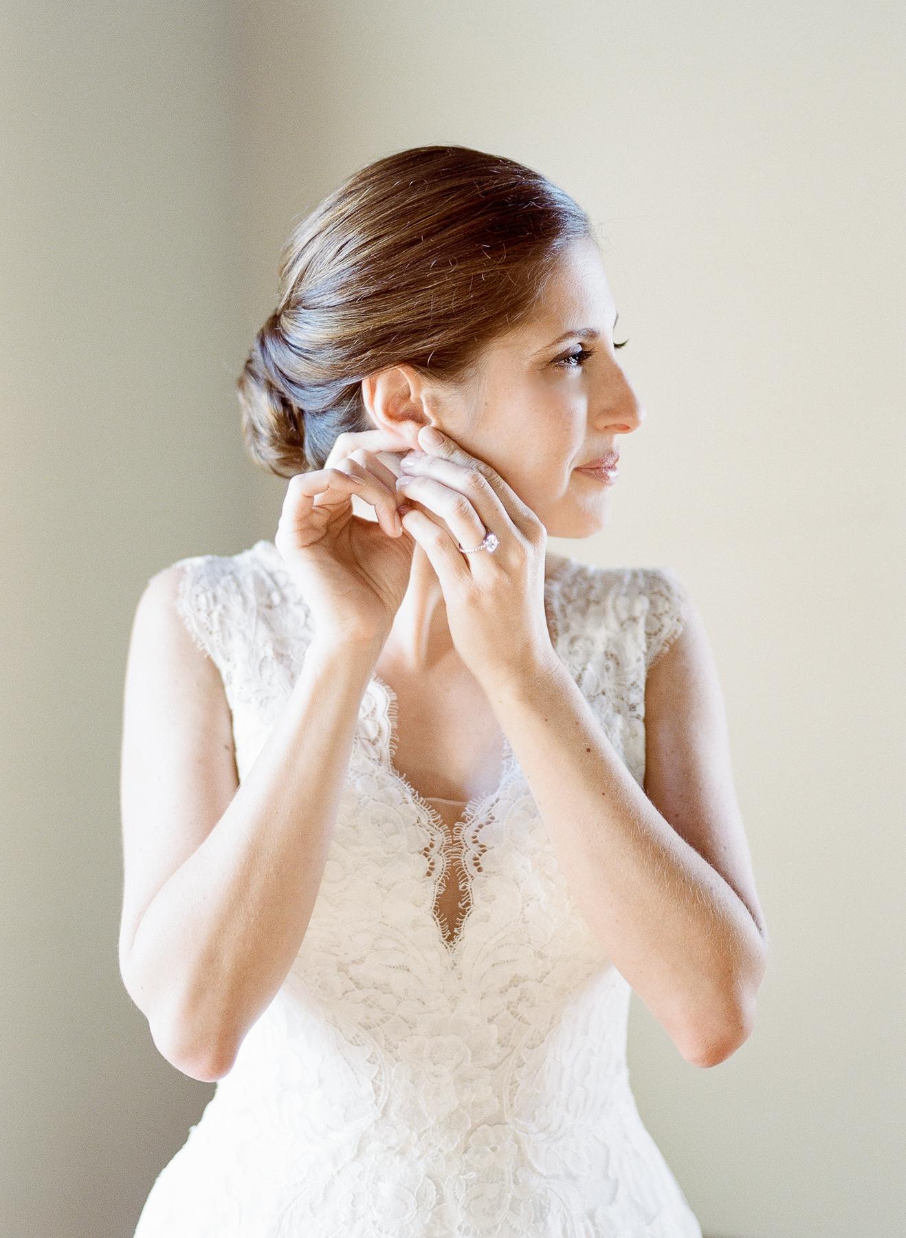 Bride putting in earrings