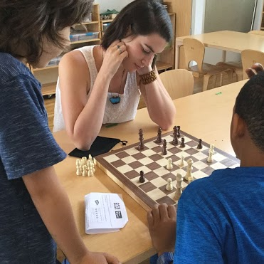 Pictured: Maggie playing chess with students.