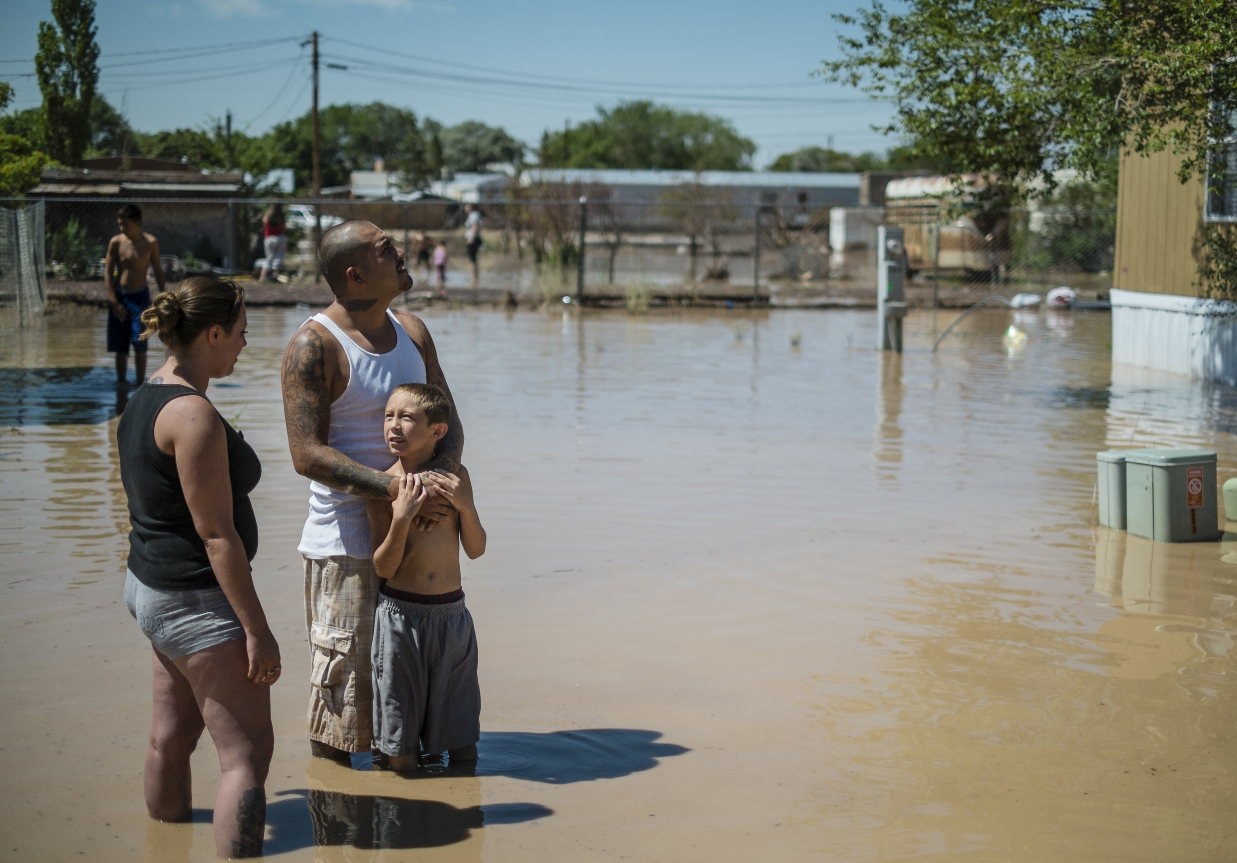 Residents of Bernalillo, New Mexico stand outside their home after being flooded by record rains.