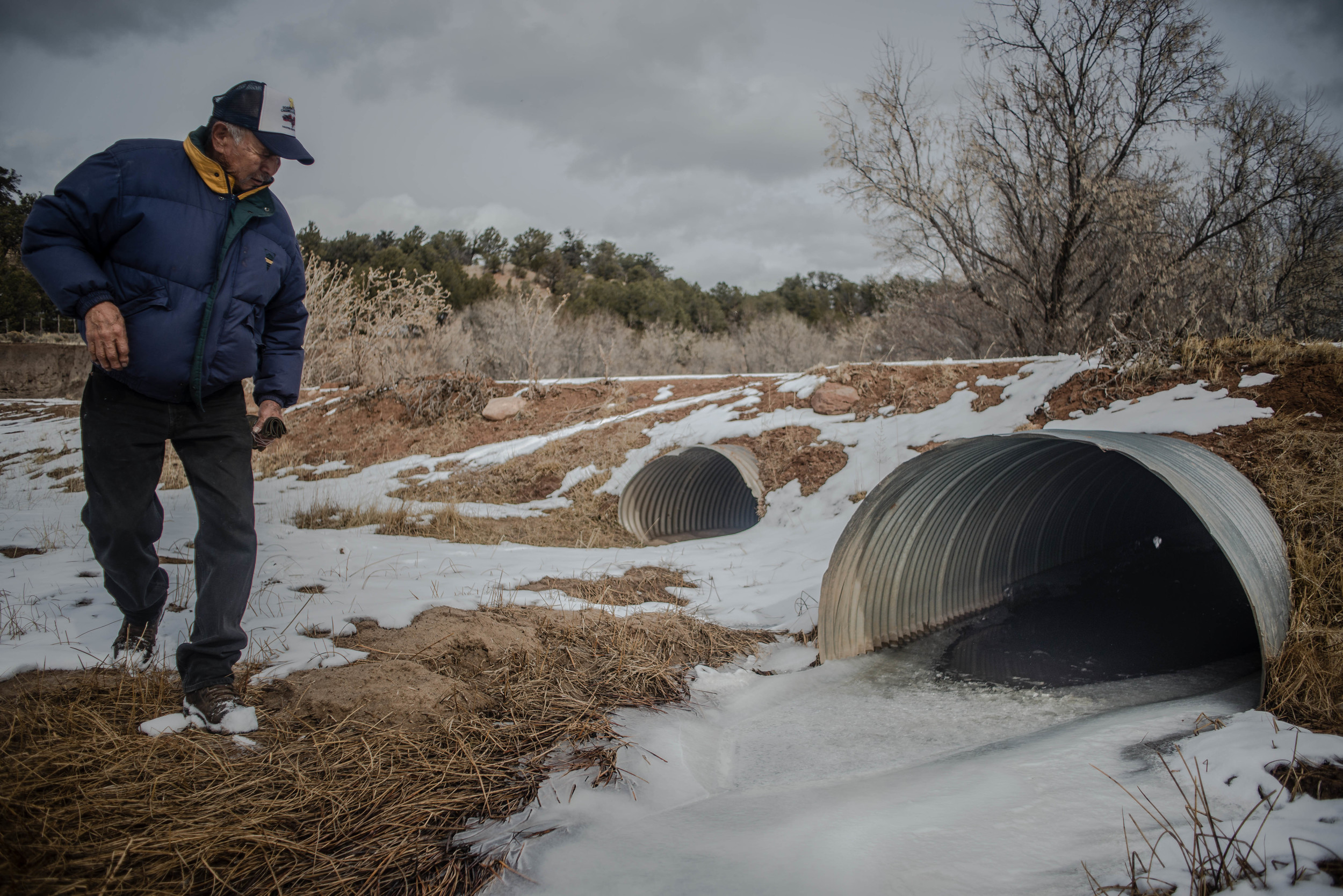 Resident Franklin Mose peers into a culvert where a 13-month-old child was found Jan. 31 in Crystal. A mother and her child were left near the culvert late at night Jan. 30 after the mother got into a fight with a woman with whom she was riding in a truck, according to the woman's uncle. (Roberto E. Rosales/Albuquerque Journal)