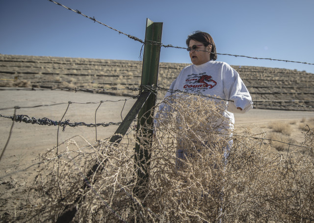 Annie Benally, a resident of the Redwater Pond Community north of Churchrock, stands in front of the abandoned Churchrock Quivira mine, where a pile containing an estimated 100,000 cubic yards of mine waste looms over homes in the Navajo community. (Roberto E. Rosales/Albuquerque Journal)