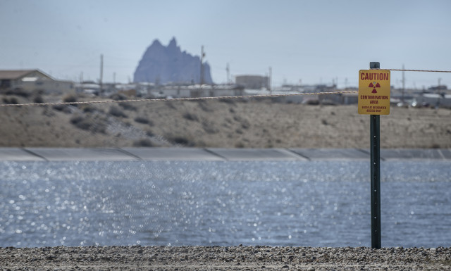 The U.S. Department of Energy operates this evaporation pond just south of the former Shiprock Mill to prevent uranium contaminated water from seeping into groundwater. The iconic Shiprock looms in the background. (Roberto E. Rosales/Albuquerque Journal)