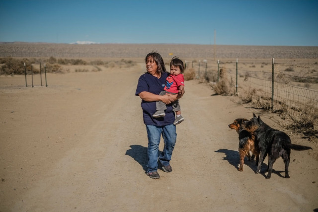 Cora Perry with her one year old Malichi Bryan walking in her front yard which sits next to the former site of a mill in Shiprock. (Roberto E. Rosales/Albuquerque Journal)