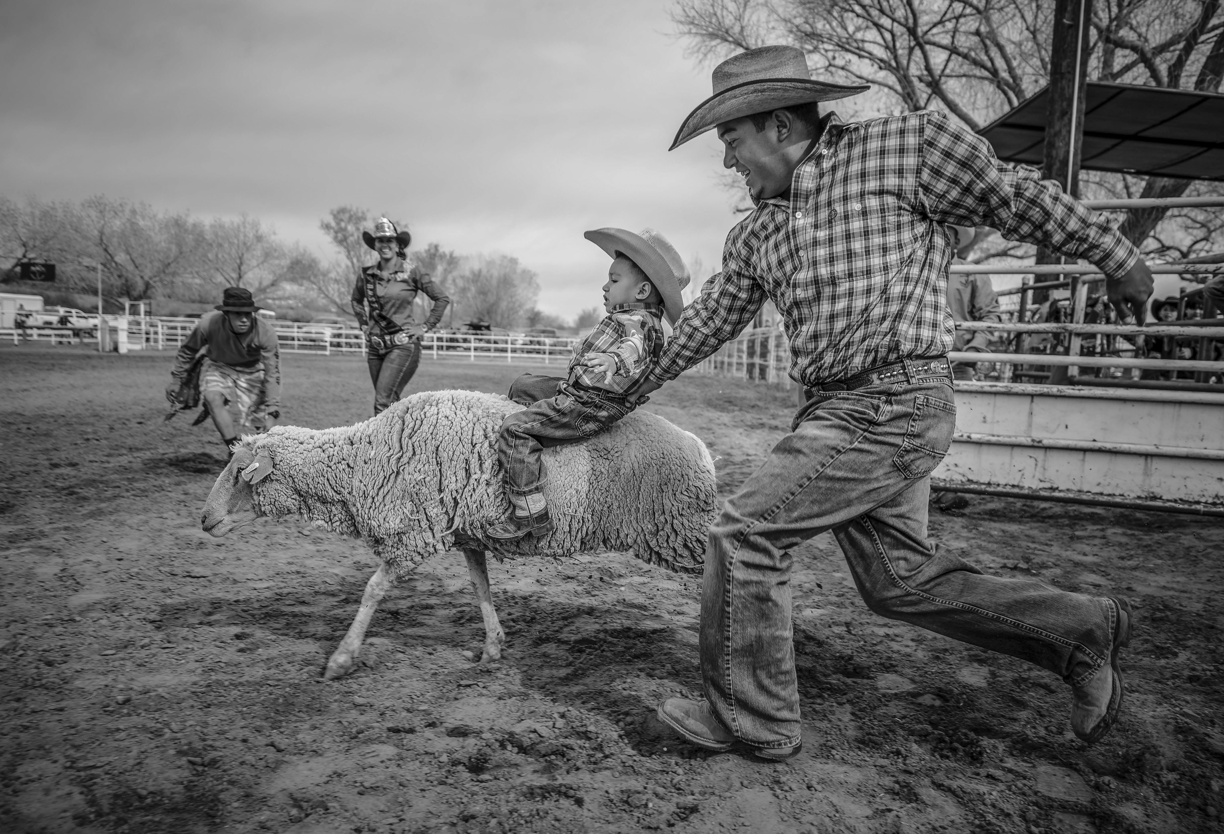 Antonio Padilla helps his 2-year-old son Jayden Padilla hang on to a sheep during the mutton-busting contest at Saturday's first Youth Day Rodeo. Mutton busting is a tamed-down version of bull riding for kids 6 and younger, according to a spokeswoman. (Roberto E. Rosales/Albuquerque Journal)