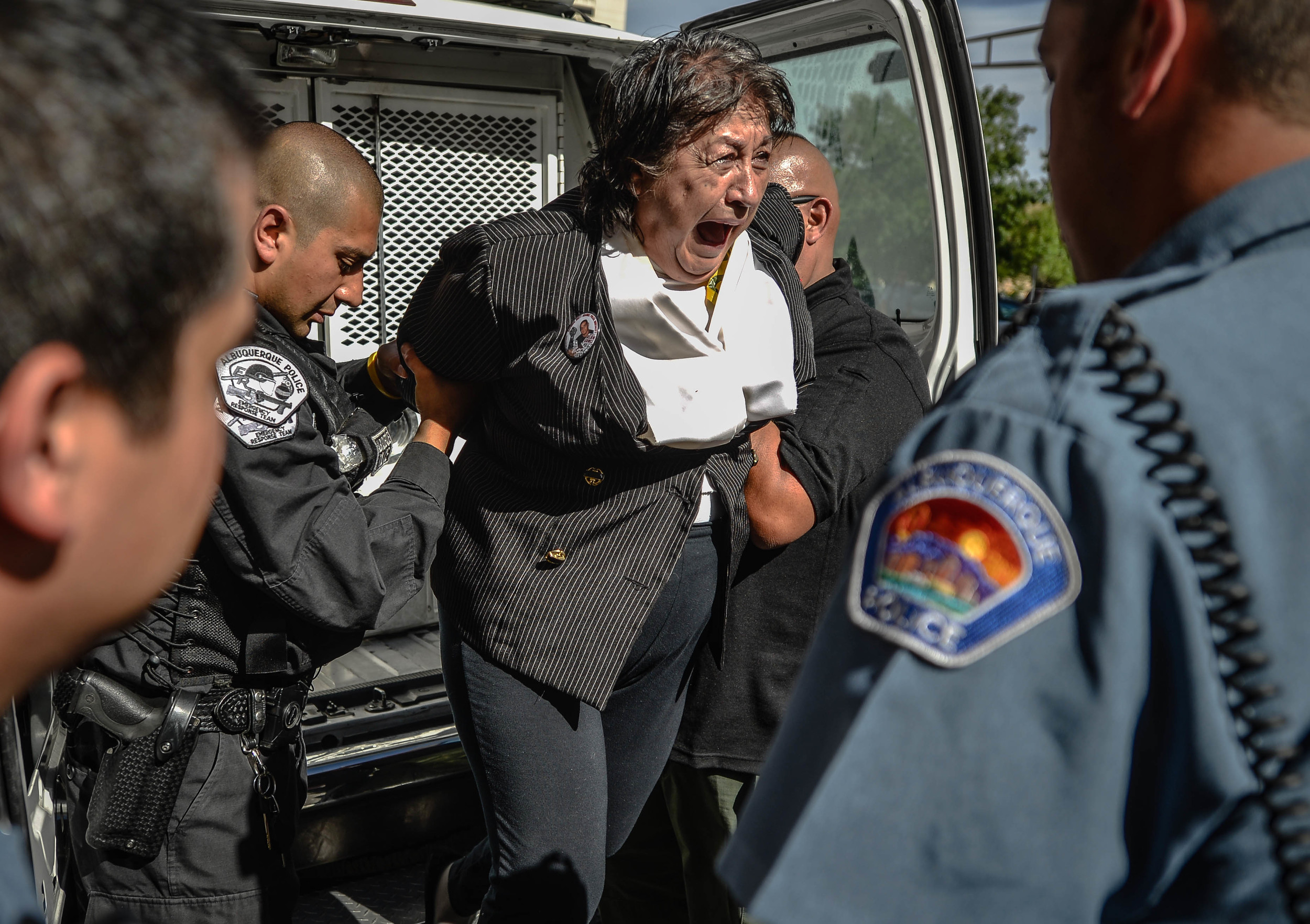Protester Nora Anaya is taken to the downtown detention center after being arrested. Anaya's nephew was killed several years ago by APD. She chained herself to a structure near the mayor's office. (Roberto E. Rosales/Journal)