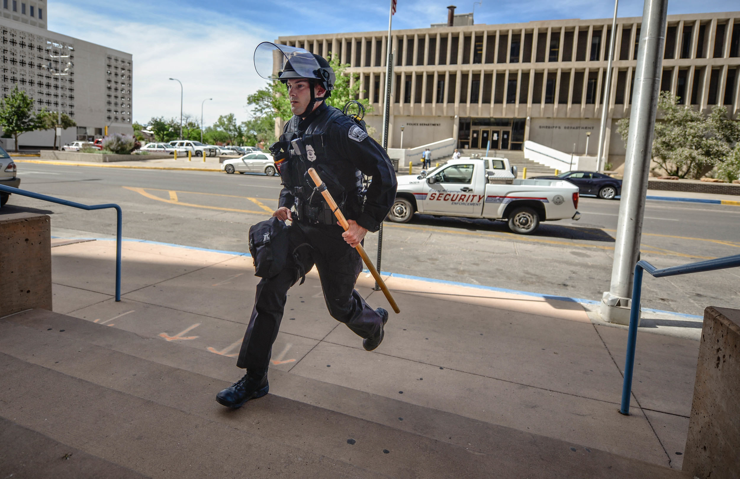 An Albuquerque Police officer runs up to the Mayor's office to arrest protesters.