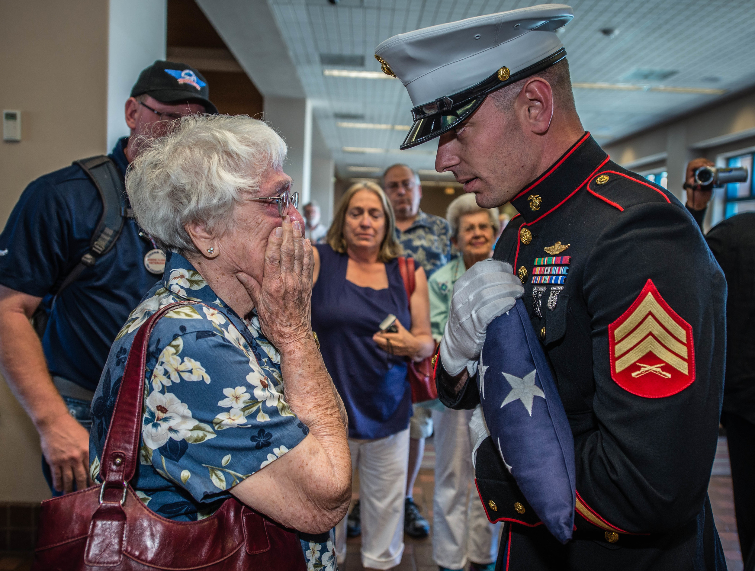 Marine Corps Sgt. Nicholas McCreary presents an American flag to Charlotte Clark of Albuquerque on Friday at the conclusion of an Honor Flight, during which 22 New Mexico World War II veterans returned from an all-expense-paid trip to visit the National World War II Memorial in Washington, D.C. Clark's husband, Arthur Clark, had signed up for the Honor Flight but passed away in April. She was also presented a framed photo of her husband in his World War II Marine uniform. (Roberto E. Rosales/Albuquerque Journal)