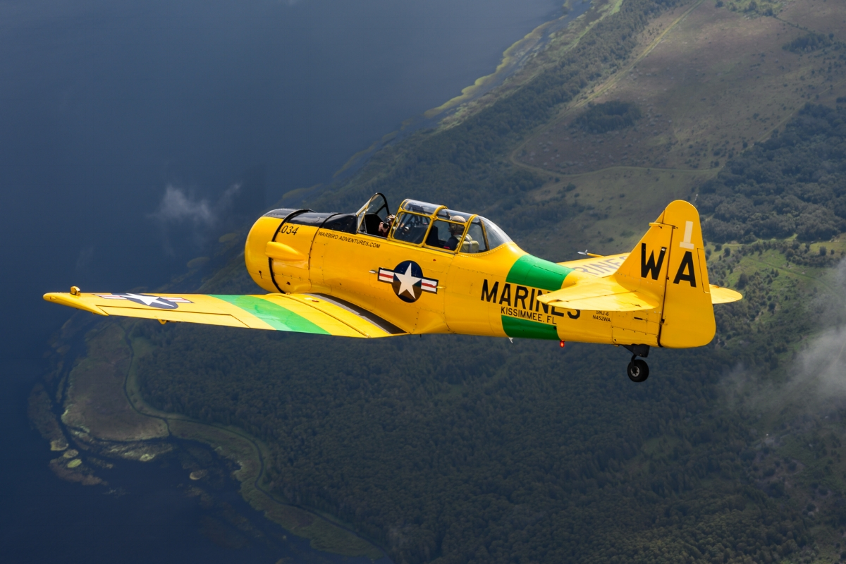 The lead T-6 turns over the lakes south of Kissimmee as my fellow photographer shoots back at us with a Nikon Z7