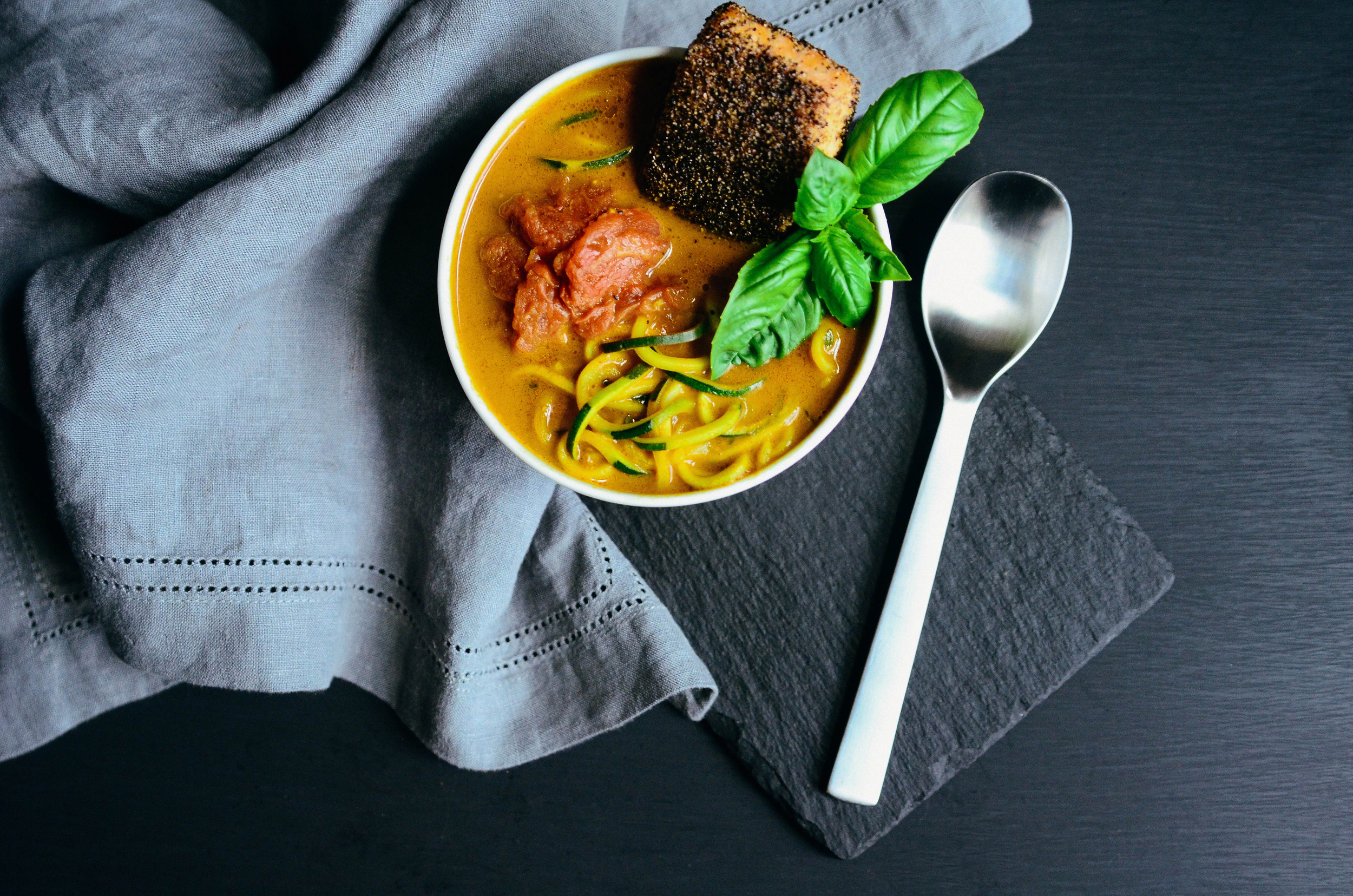 Black Pepper Salmon and Coconut Curry Zucchini Noodle Bowl with Stewed Tomatoes topped with Basil | Seed Plant Water Grow