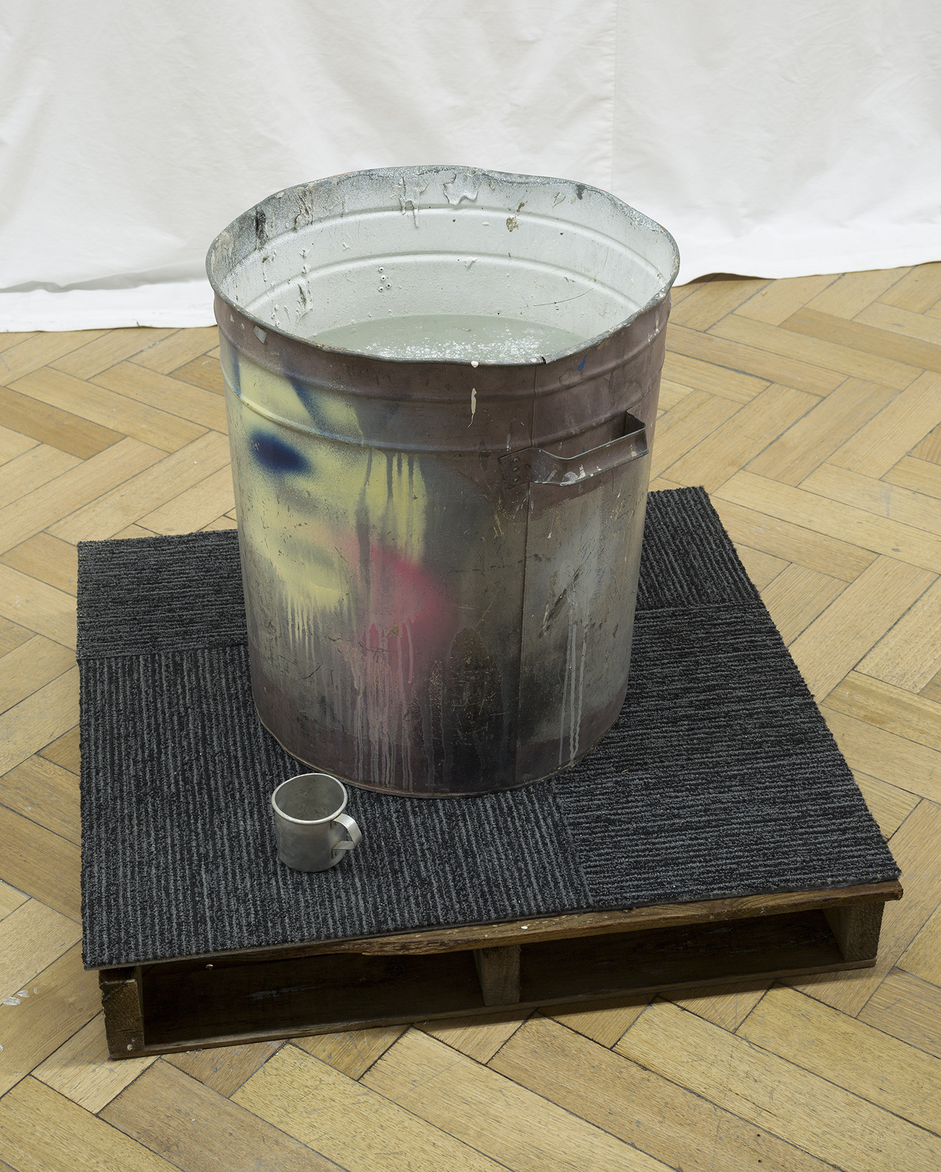 Swish or Swill, 2017. Found tin can, found tin cup, crate, carpet tiling, water and asbestos like talcum powder, 1200 X 900 X 1200 mm. Image: Christian Capurro