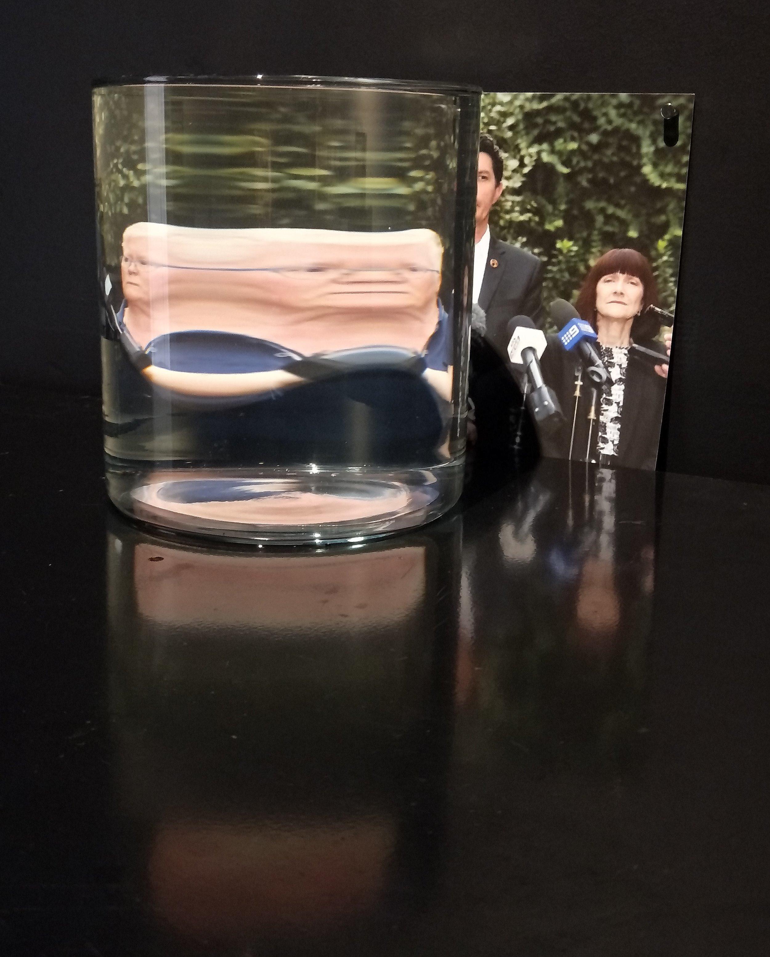 Scott Ludham's Departure: Scott Ludham google image search  2017, paint, steel, inkjet photograph on Museo Rag, google location https://cdn.newsapi.com.au/image/v1/427b9732a143de339d92d4ba284eed88?width=650, water, glass vessel, light, 67cm x 45cm x 140mcm.