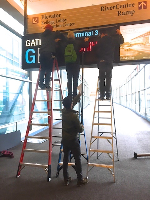 Local 490 Art Dept hangs new signage to transform a St.Paul skyway into an airport.