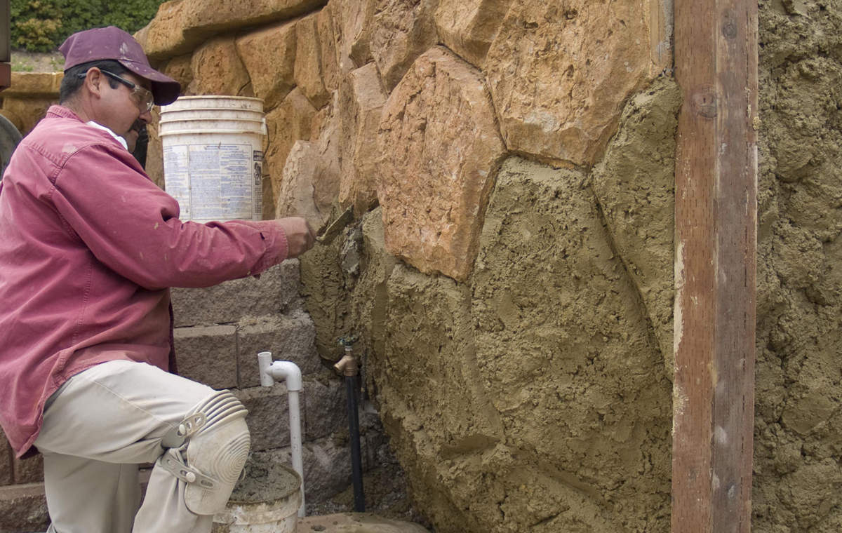 Enviroscaping's faux-stone master Inocencio Juarez adds color to one of his striking handmade walls.