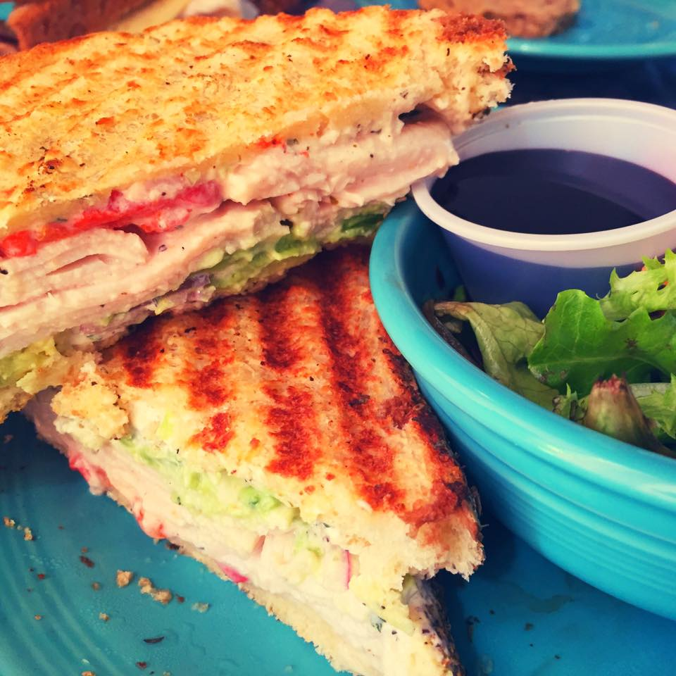 Have you tried our special panini? Toasty Parmesan bread (baked in-house!) with herbed cream cheese, smoked turkey, creamy avocado, and roasted red peppers... Served with your choice of side!