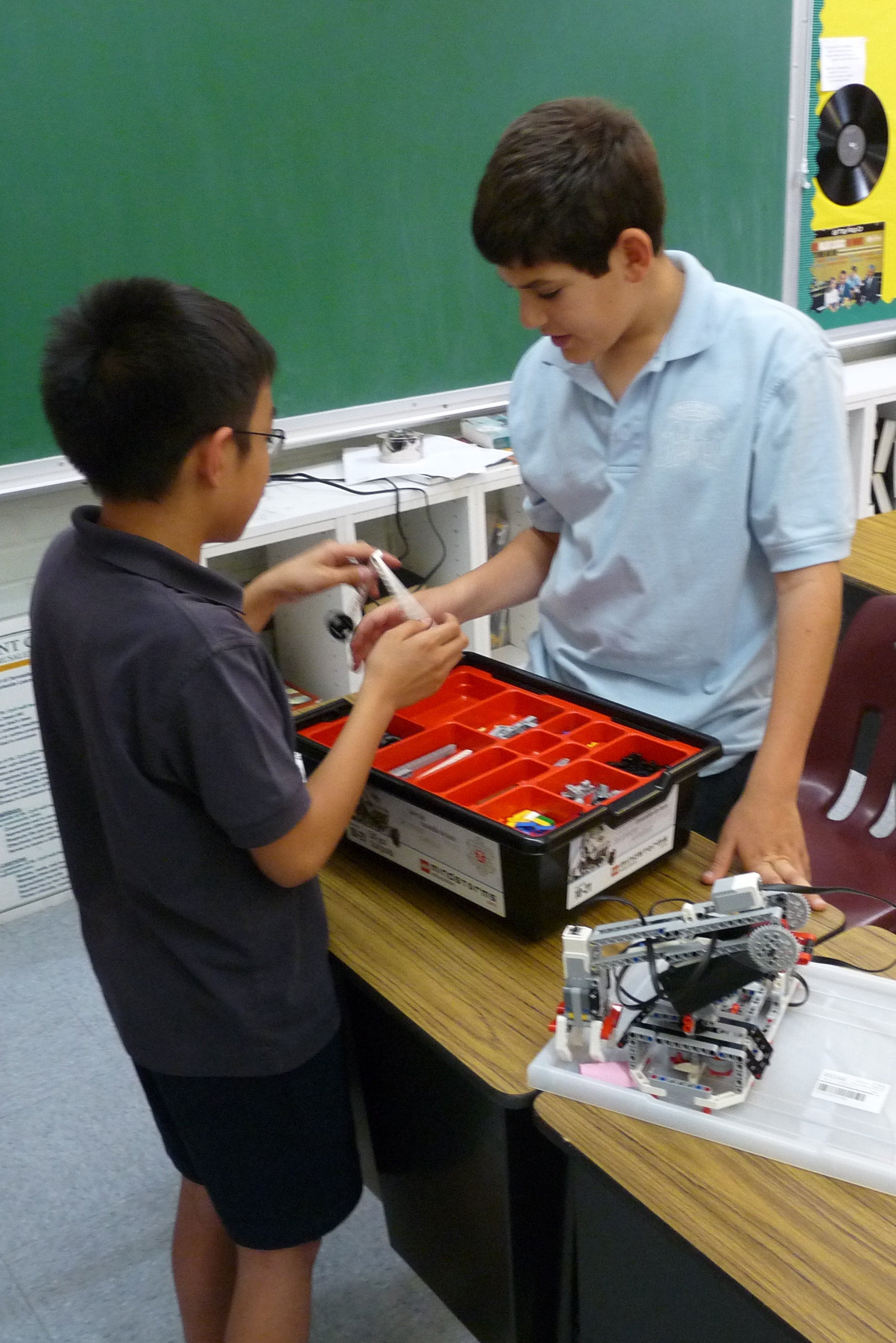 Students sorting through basic components to build a robotic mechanism