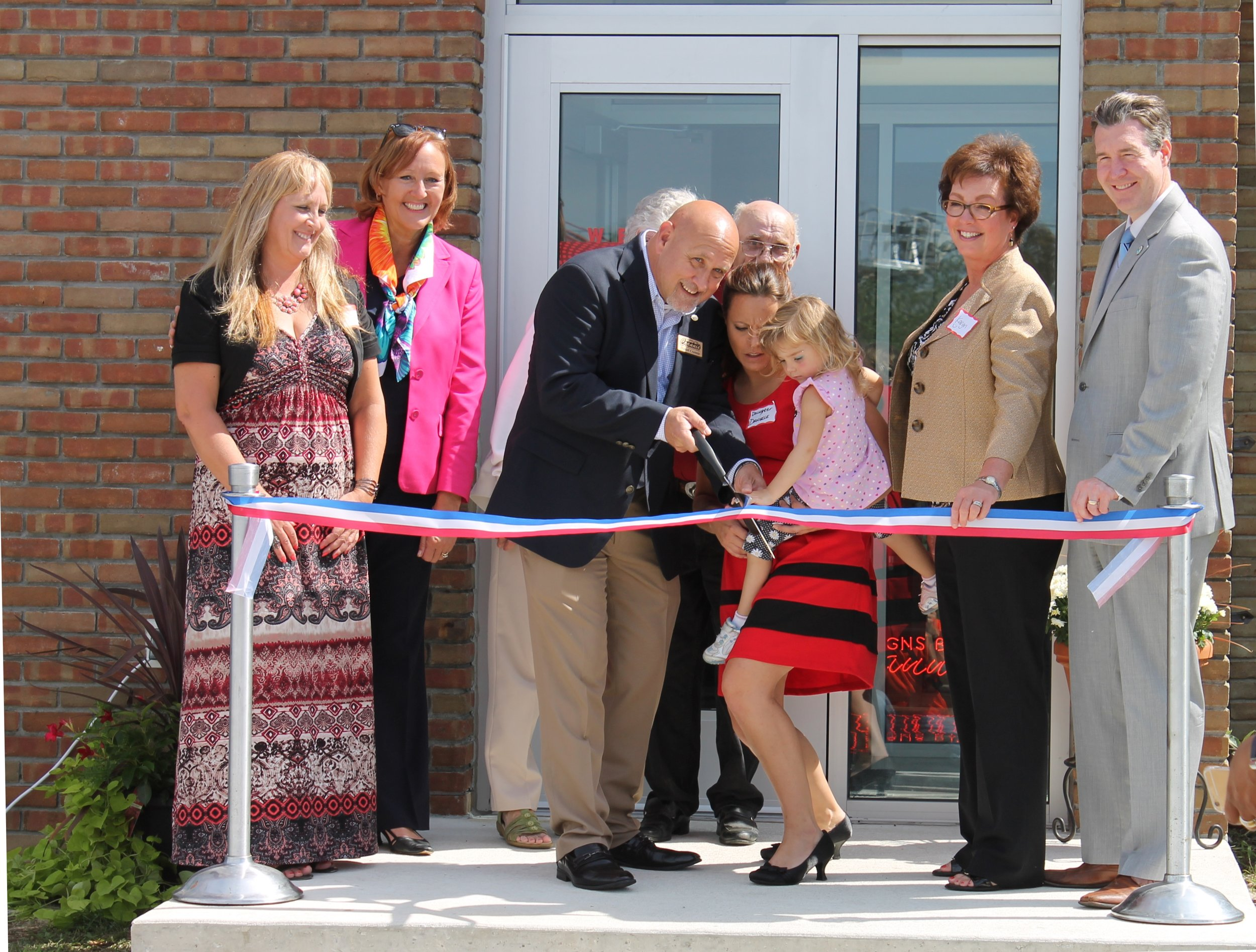 Friends, family, and local dignitaries help celebrate the grand opening of the new Signs by Crannie building in Flint Twp.