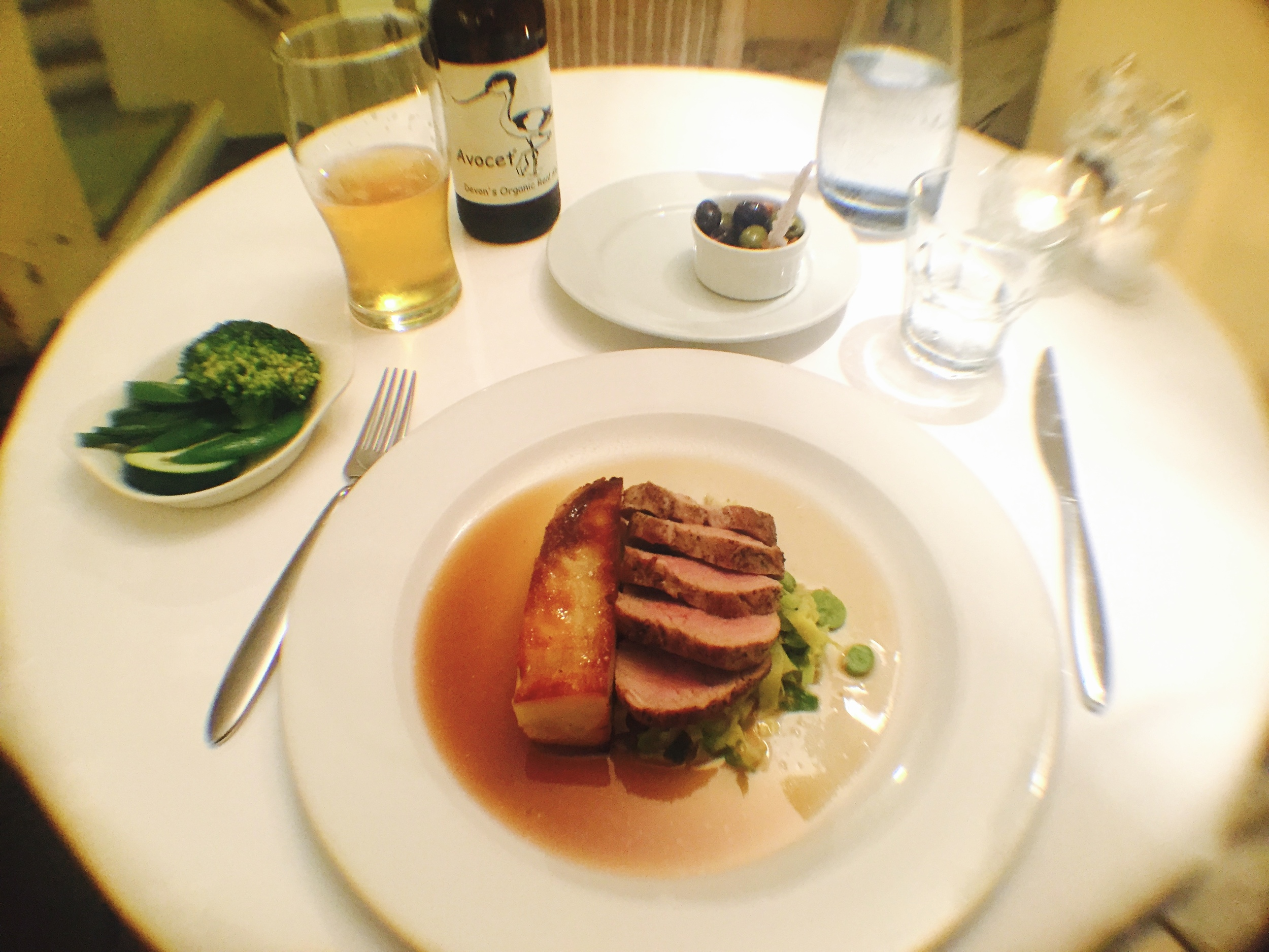 Roasted pork tenderloin, broad bean and spring cabbage, dauphinoise potato, calvados sauce and fresh green vegetables