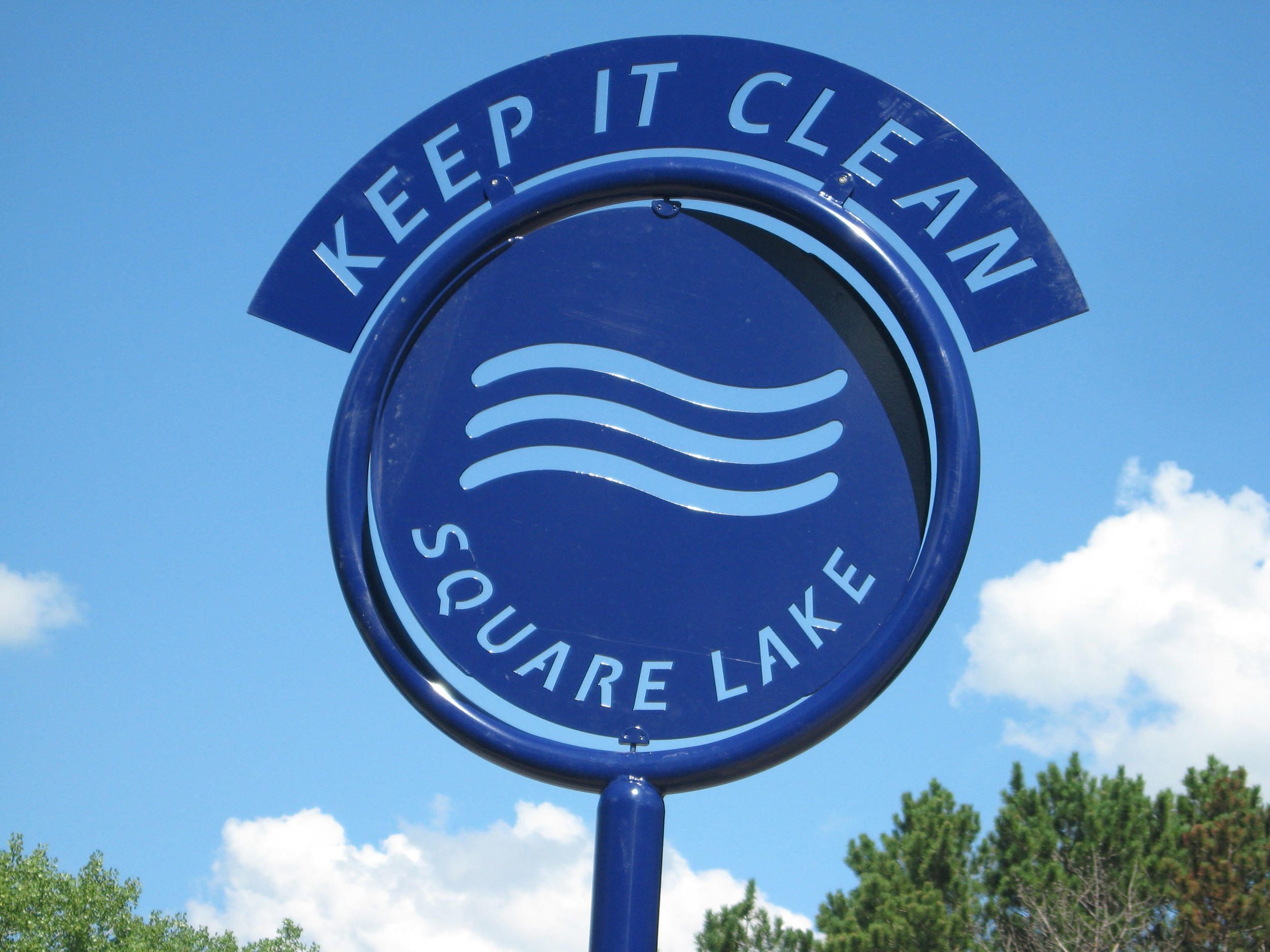 A sign marks a new demonstration project to reduce runoff from the parking lot at Square Lake Park.jpg
