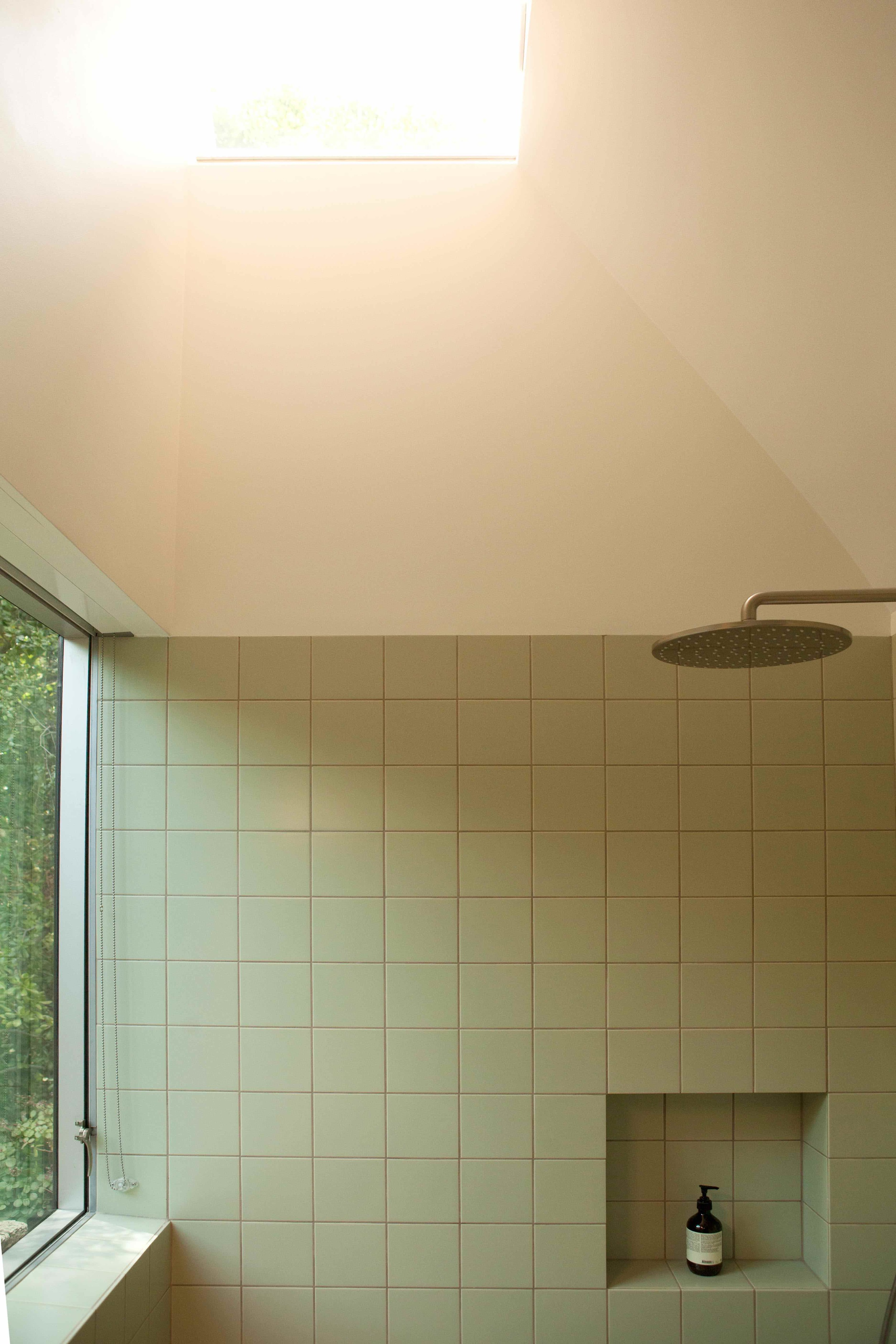 Simple clean Mosa tile in an earthy green shade wraps the lower half of the room.