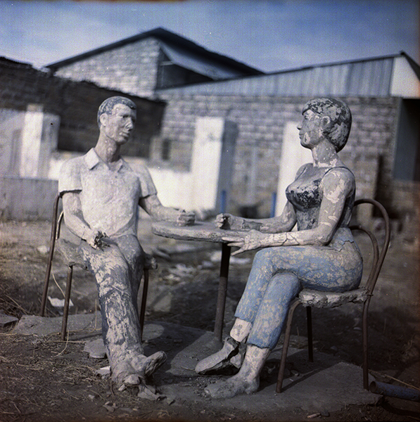Statue of two, surrounded by ruins of a place that was possibly a café years before, in Yerevan's Bangladesh district.