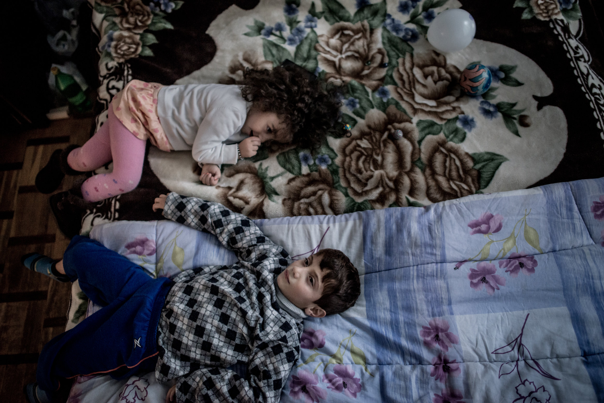 Garo Tomassian, 8,  plays with his newfound friend, Aaliyah, from Yerevan. Garo's family  - his mother, two older brothers, and sister - arrived in Armenia from Turkey's Suruc refugee camp in September 2015. His father was killed by Islamic State fighters earlier that year. They rented a house in Yerevan, and their mother Ilona found work as a tailor. The family moved to Suruc after fleeing Kobani. Note: This family is related to the family of Serop Tomassian. Serop was the brother of the killed father of this family. This family lives separately from Serop's family, in Yerevan.
