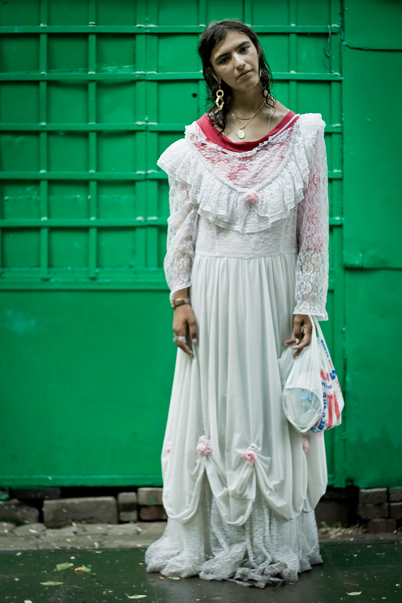 MARIAM   Mariam and I met in the street on a gloomy day. The heavy rain had just ended and she was walking in a wet wedding dress. I went up to meet her and it turned out that she could not articulate herself clearly, which did not seem important. She was not wearing the wedding dress for a special occasion, she was just going home.    Mariam later told me her relatives had sent her the dress from America, and she liked wearing it. She also showed me a picture where she posed in this dress and a bucket of flowers in a photo studio.