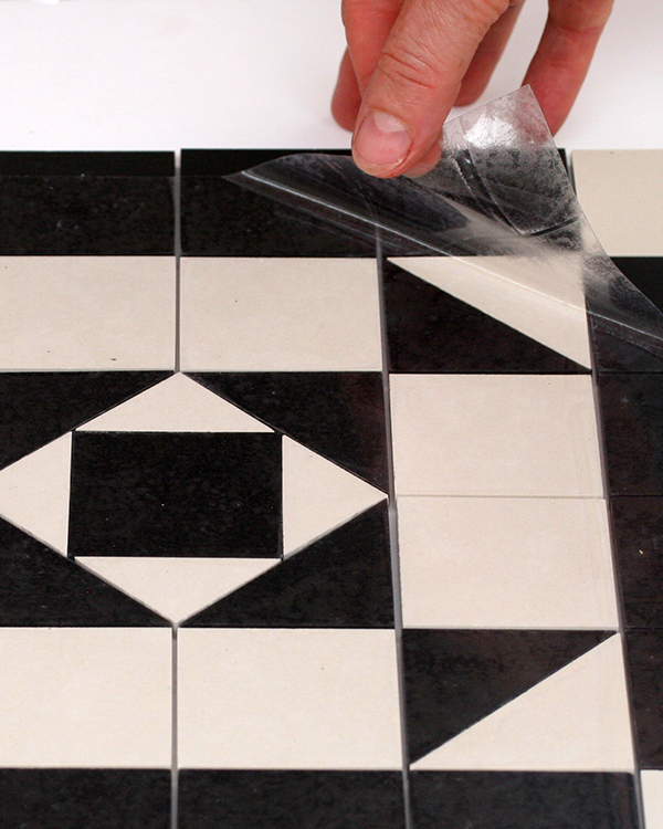 THE PANELS ARE FACED WITH A CLEAR FLEXIBLE ADHESIVE FILM. THIS ALLOWS FOR VERY EASY HANDLING AND FAST FIXING.  EADY TO LAY PANELS  Our sheeted mosaics are all made in the studio to order. The chequer designs are sheeted as panels of 6 tiles x 6 tiles (30.5cm square) with a narrow 1 to 2mm grout joint. The rectangles for the border and triangles for the main designs and chequers are all hand cut.  The panels are faced with a  clear flexible adhesive film . This allows for very easy handling and fast fixing:  strong yet easy to remove  protects the face of the mosaics whilst being laid  allows for complete adhesion and a stronger bond  enables the tiler to see how each sheet is adhering to the cement bed  ensures the face of the tile is protected before grouting