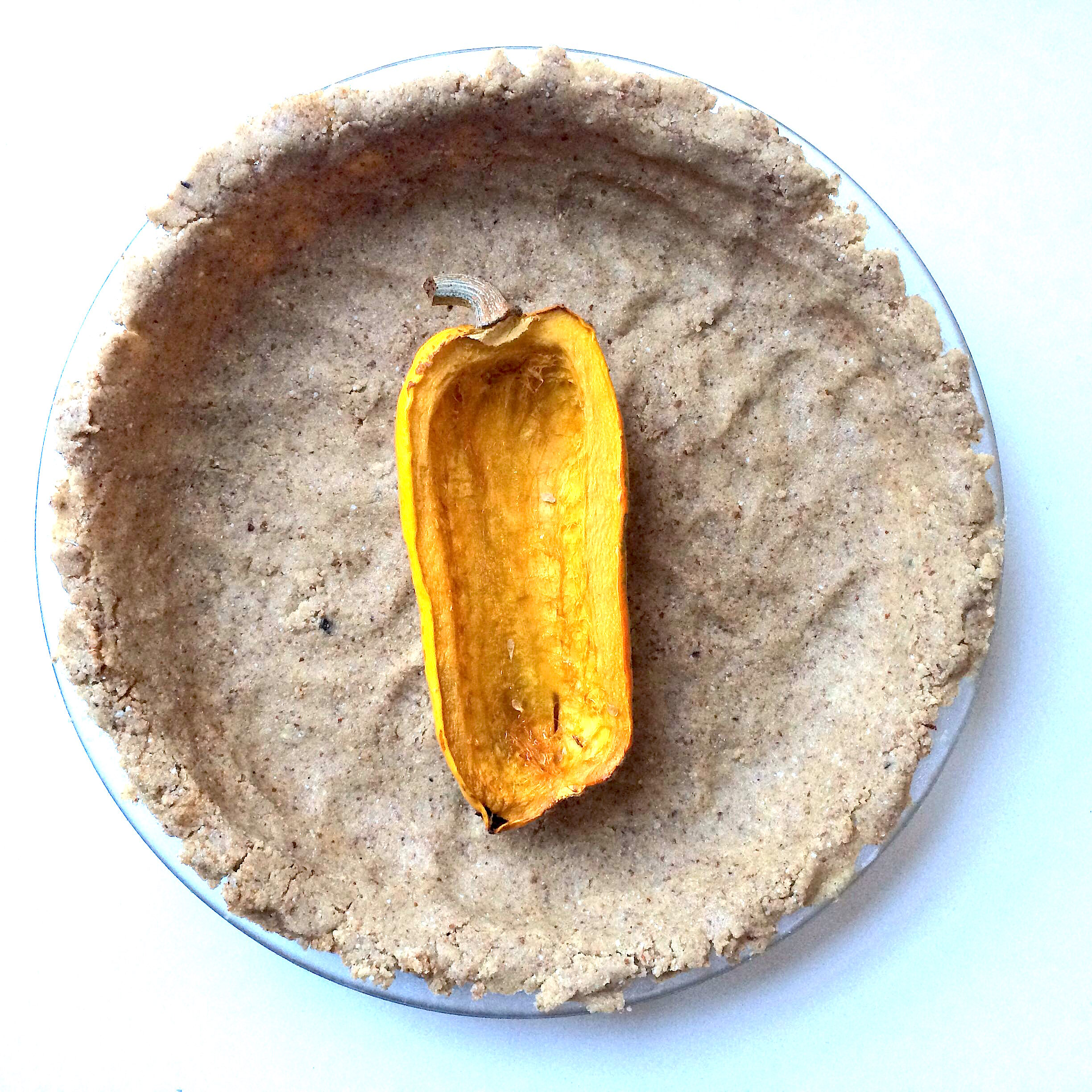 Delicata squash roasted, and pie crust prepared and getting spread on the pie dish.