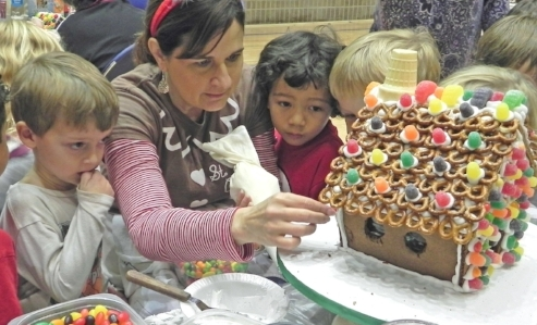 Children watch gingerbread house decorating.
