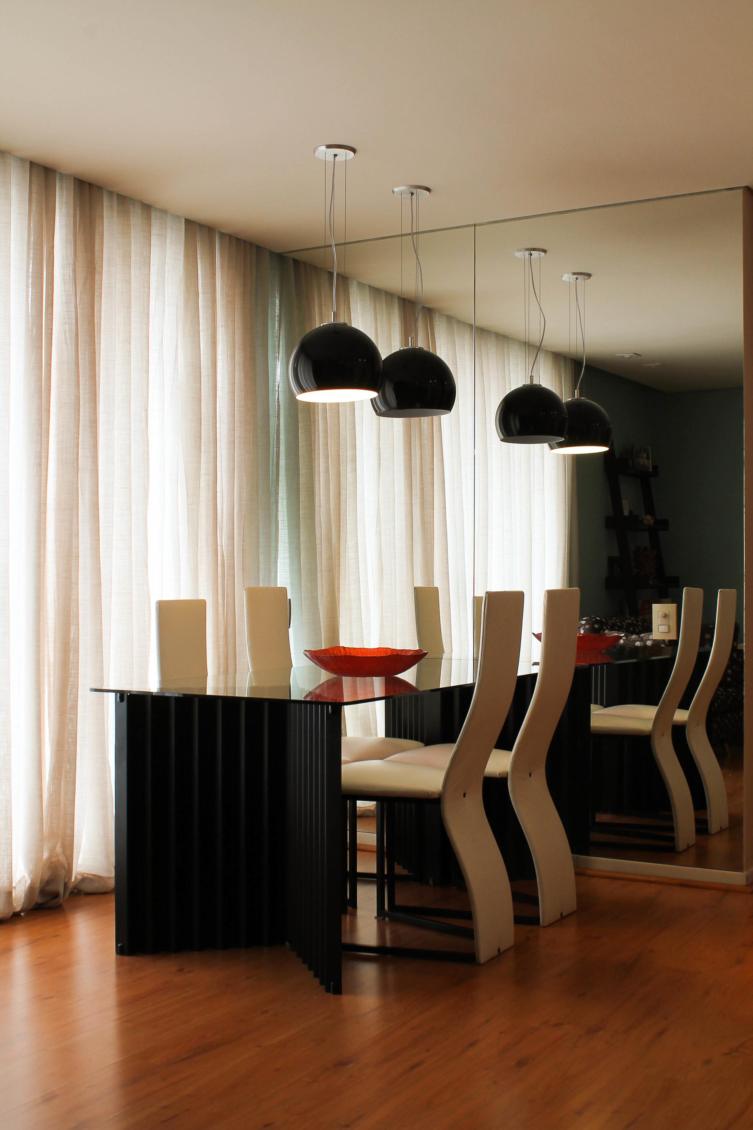 Sala de jantar iluminada por pendentes.