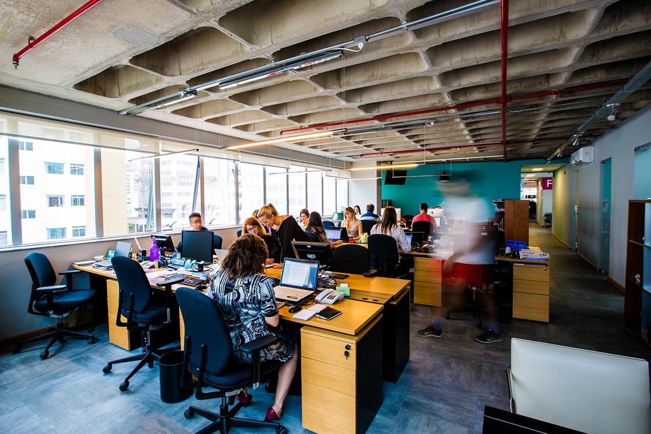 Perspectiva do salão do Staff com salas de reunião. Fazer uso de materiais aparentes (como concreto, madeira e a laje nervurada) foi uma das premissas para a concepção do projeto.