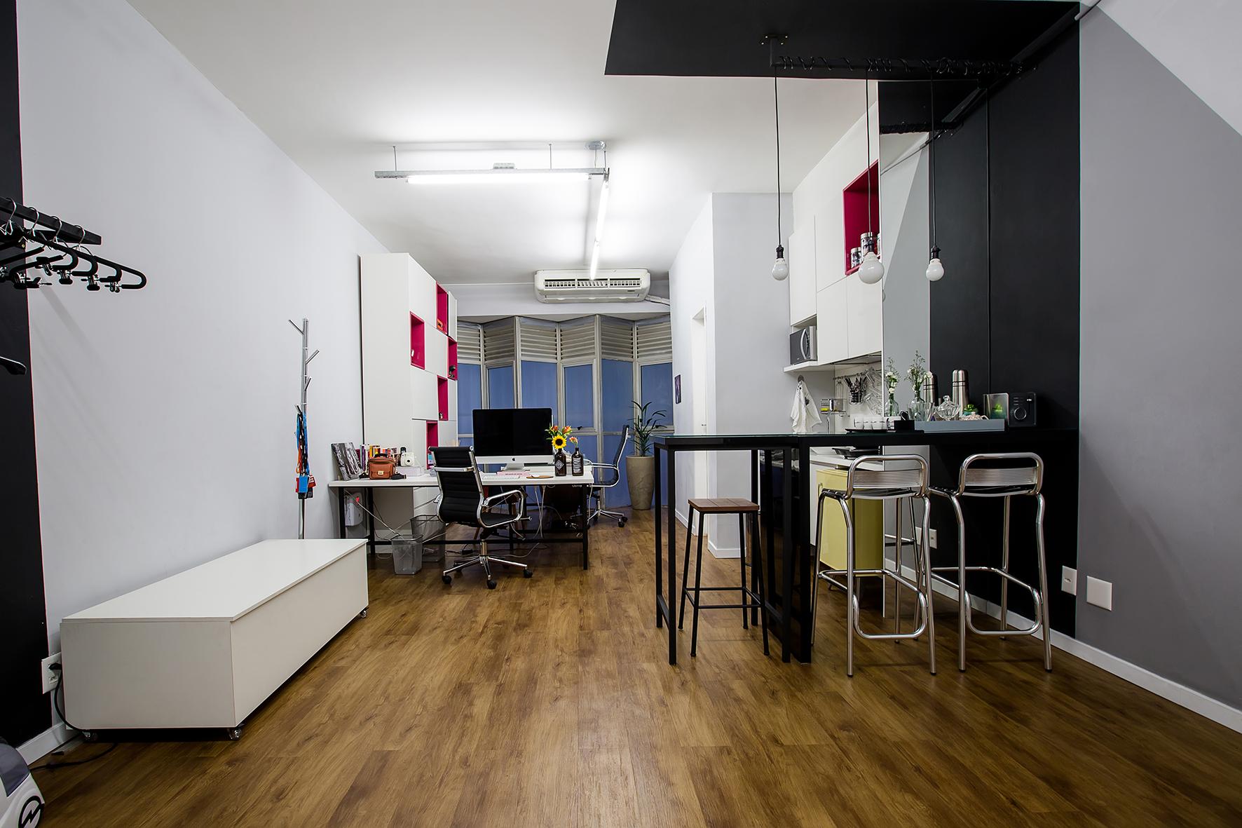 Estúdio com piso vinílico amadeirado, pintura das paredes com detalhes em cinza Prata Fina (Coral) e faixas pretas. Lâmpadas instaladas em eletrocalhas.