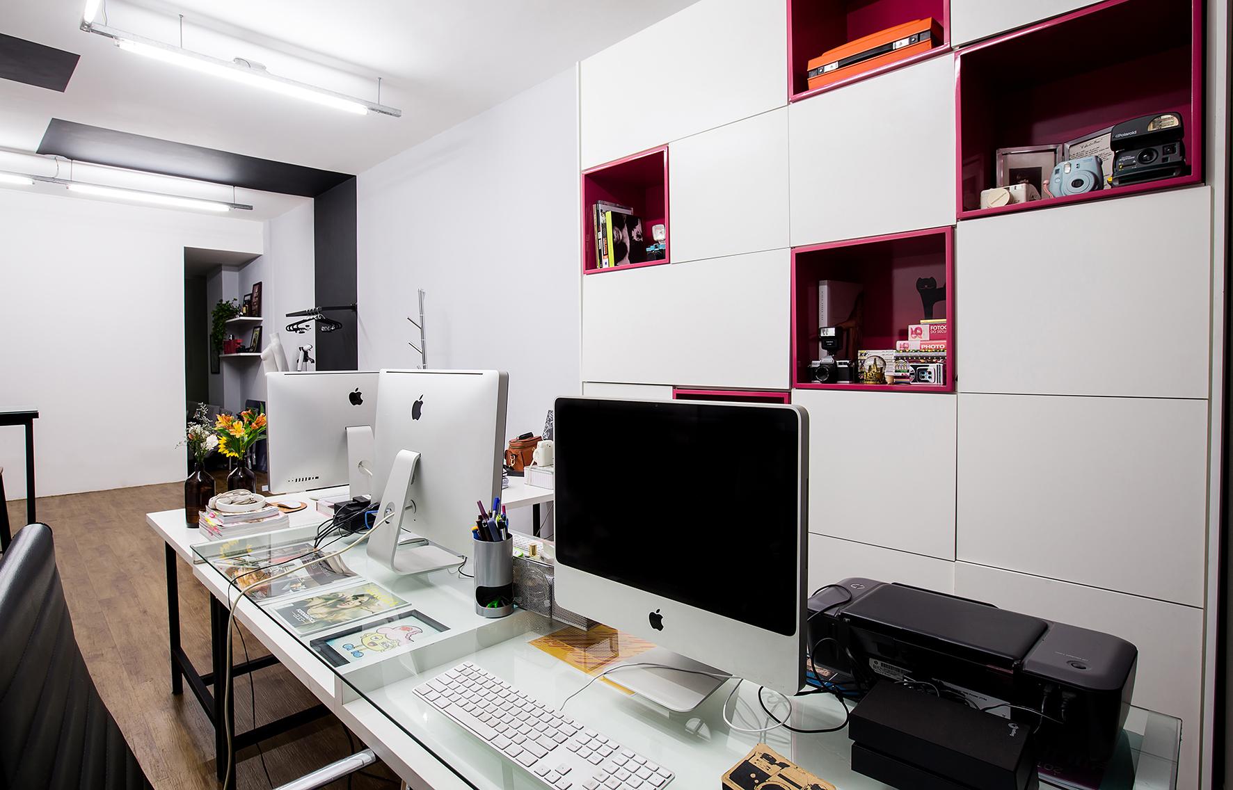 Escritório com armários de mdf branco e nichos com laca brilhante rosa, mesas com estrutura metálica e tampos de mdf e vidro.