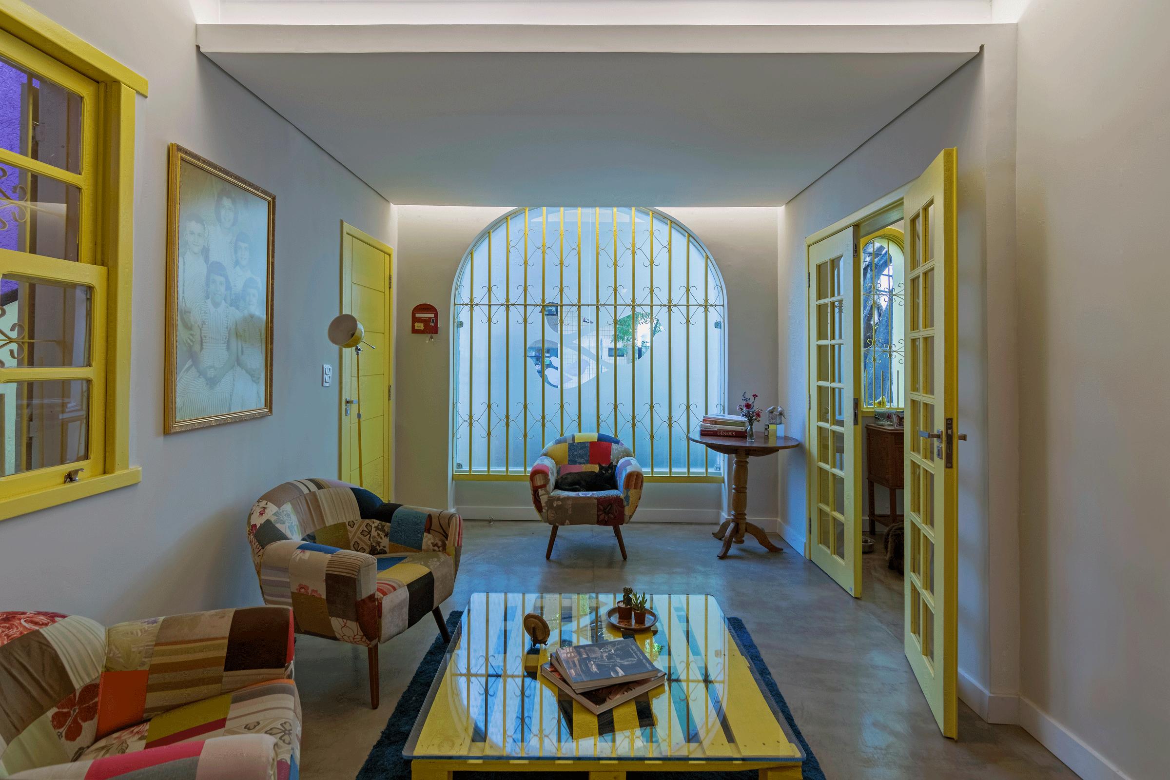 A grande janela em arco marca tanto a fachada quanto a sala de entrada. À esquerda, um quadro com os primeiros moradores da casa.