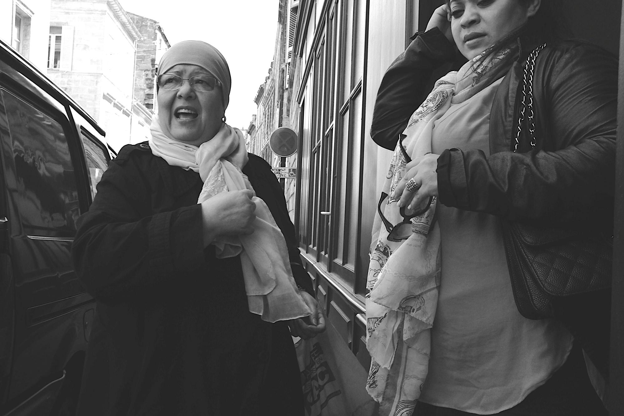 Expression du bien-vivre. Deux femmes pleines de vie en grande conversation dans le quartier Saint-Michel de Bordeaux. L'image vivante de l'échange, du bien-vivre entre différentes cultures, couleurs de peau ou de religion. Les rondeurs de ces deux femmes apportent une forme de douceur et de sérénité très maternelle. Techniquement, la photo n'était pas simple à réaliser car c'était un one shot et j'ai eu la chance de saisir ces deux visages expressifs.  Expression du bien-vivre. Quartier Saint-Michel | Bordeaux | France Fuji X100S | 23ƒ2 (35 equivalence) Photos sur le site 500px  ©Thierry Lothon 2014.