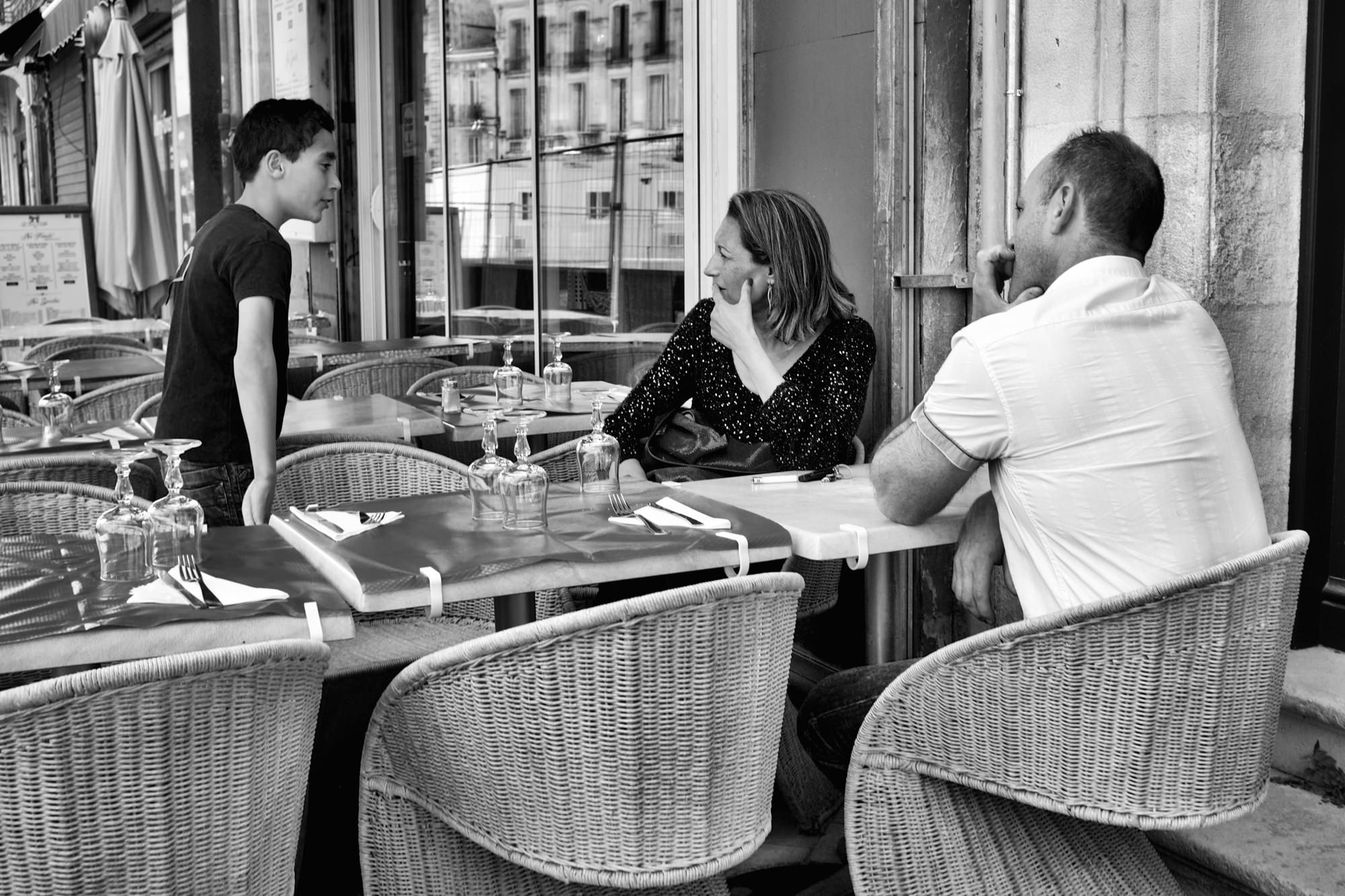 Conversation bienveillante J'éprouve un bien-être à me promener dans le quartier Saint-Michel de Bordeaux. Un quartier où se côtoient différentes cultures, races, couleurs et de nombreuses couches sociales. Si vous aimez aller à la rencontre des gens, je vous conseille ces lieux. Au détour des rues que je traversais, je suis passé devant ce restaurant, face à la basilique Saint-Michel, où un couple de touristes faisait la conversation avec un jeune adolescent qui pourrait être le fils du patron. J'ai senti la scène prise à la fois d'une grande simplicité et d'une force bienveillante de ce couple à l'égard de ce jeune garçon. Mon appareil photo, un Fuji X100S, s'est naturellement tourné vers cette scène particulièrement simple, mais d'une grande force photographique       Conversation bienveillante Basilique Saint-Michel | Bordeaux | France Fuji X100S | 23ƒ2 (35 equivalence) Photos [sur le site 500px](http://500px.com/thierrylothon/sets)  ©Thierry Lothon 2014.