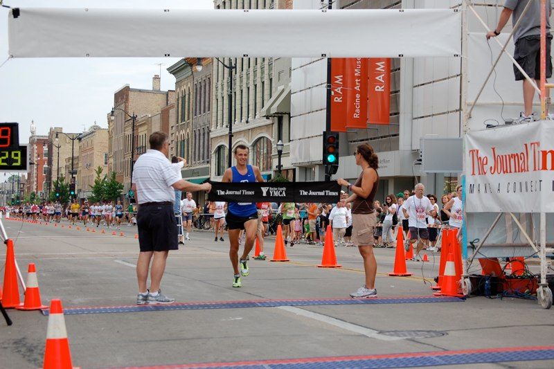 2012 winner crossing the finish line in Downtown Racine. Photo courtesy of lighthouserun.com.