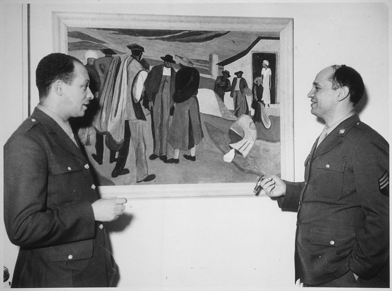 """""""Sgt. Romare Bearden, noted young Negro artist whose paintings have been exhibited in galleries and museums in several metropolitan centers ... is shown (right) discussing one of his paintings,  Cotton Workers,  with Pvt. Charles H. Alston, his first art teacher and cousin... Both Bearden and Alston are members of the 372nd Infantry Regiment stationed in New York City. """"  (From Wikipedia Commons)"""