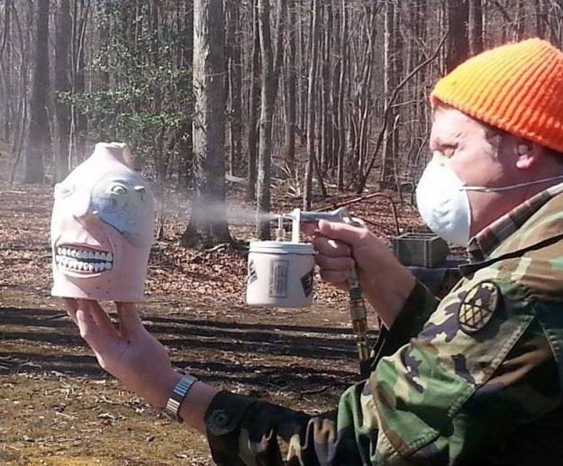 Stacy lambert Spraying glaze for final firing.jpg