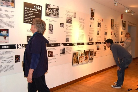 Kate Worm, the exhibit's' creator and curator, reviews the 1944 time line of local and national events in the Museum's first year. Kristina Anthony, HMA's Exhibitions Manager, created the timeline.