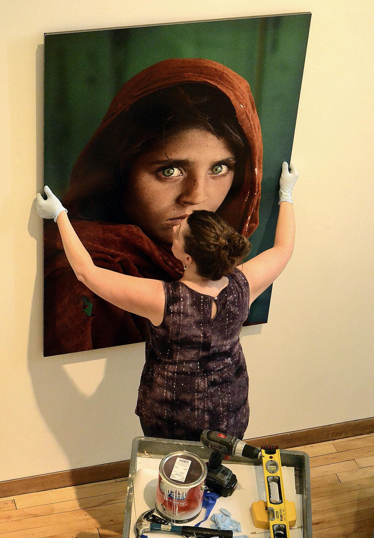 Kristina hanging Steve McCurry's  Afghan Girl.  Photo by Robert Reed.