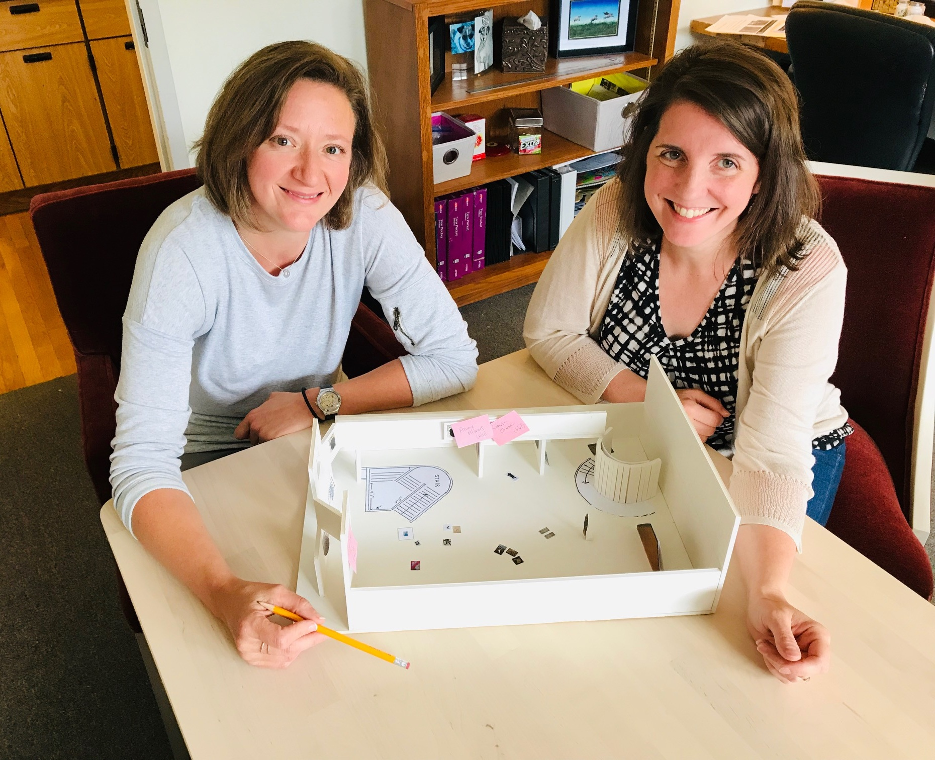 Clarissa and Kristina play with a model of the Coe Gallery discussing an upcoming exhibition