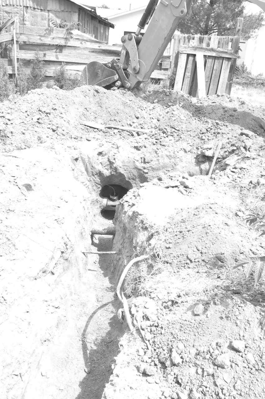 Early May - 14 May: You can see the tunnel that Josh dug by hand here, for our sewer line. And the mechanical arm shows the city opening up the sewer main.