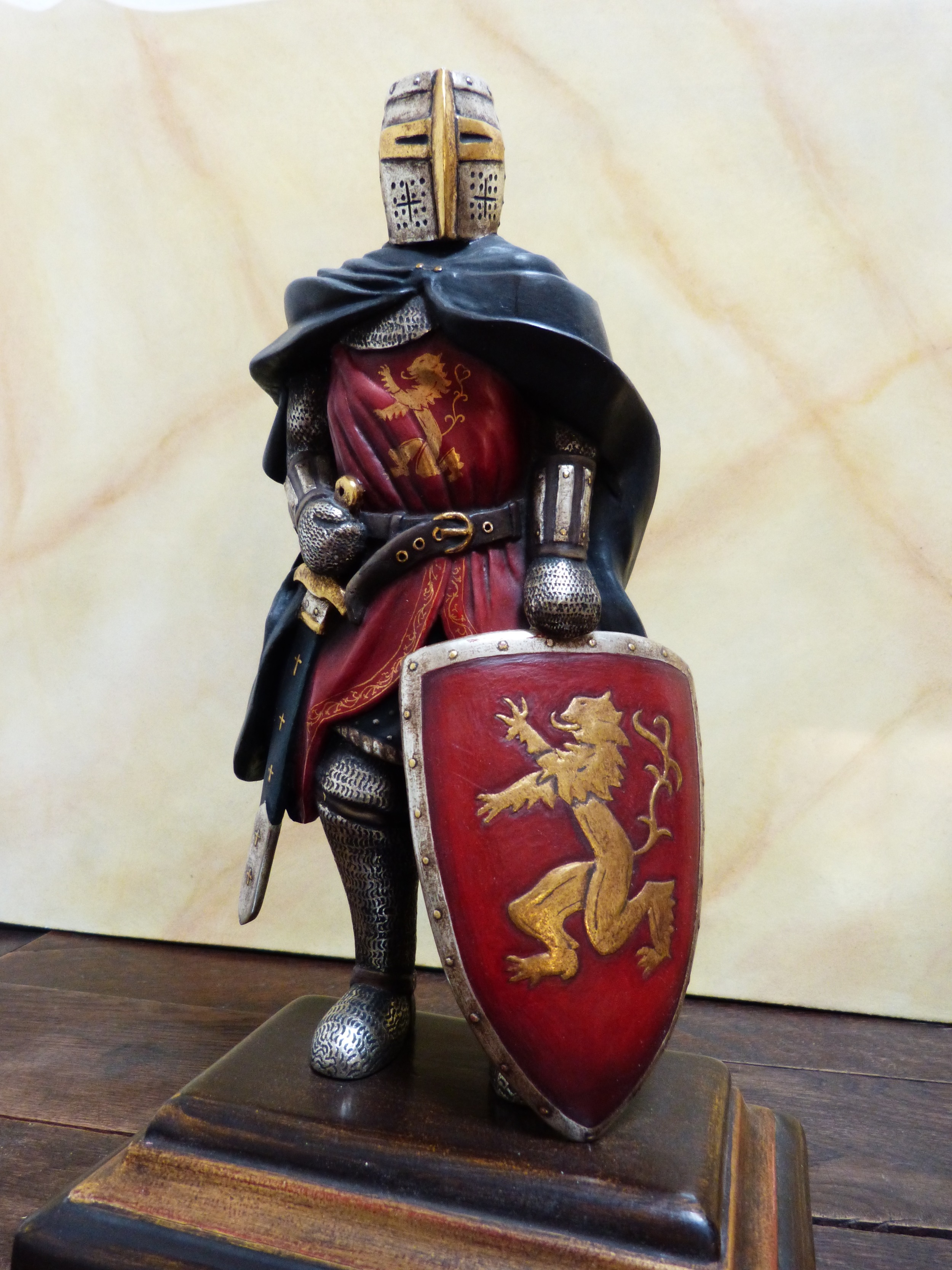 Diese Ritterskulptur misst ca. 30 cm und ist auf einem Holzsockel montiert. Es handelt sich hier um einen englischen Kreuzfahrer, wie sie zu Anfang des 13. Jahrhunderts auf Kreuzzug gingen. Die Rüstungsteile sind echtvergoldet. Das Wappentier und die Ornamente auf dem Wappenrock sind von Hand ausradiert. Alle farbigen Teile sind mit eigens hergestellter Farbe nach Licht- und Schatteneffekt gemalt.