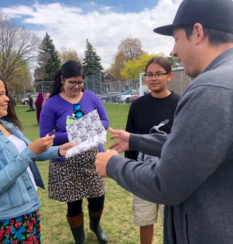 YABP students autographing Tommy Orange's copy of Indigenous Originated at South High's end of the All Nations end of the year powwow.