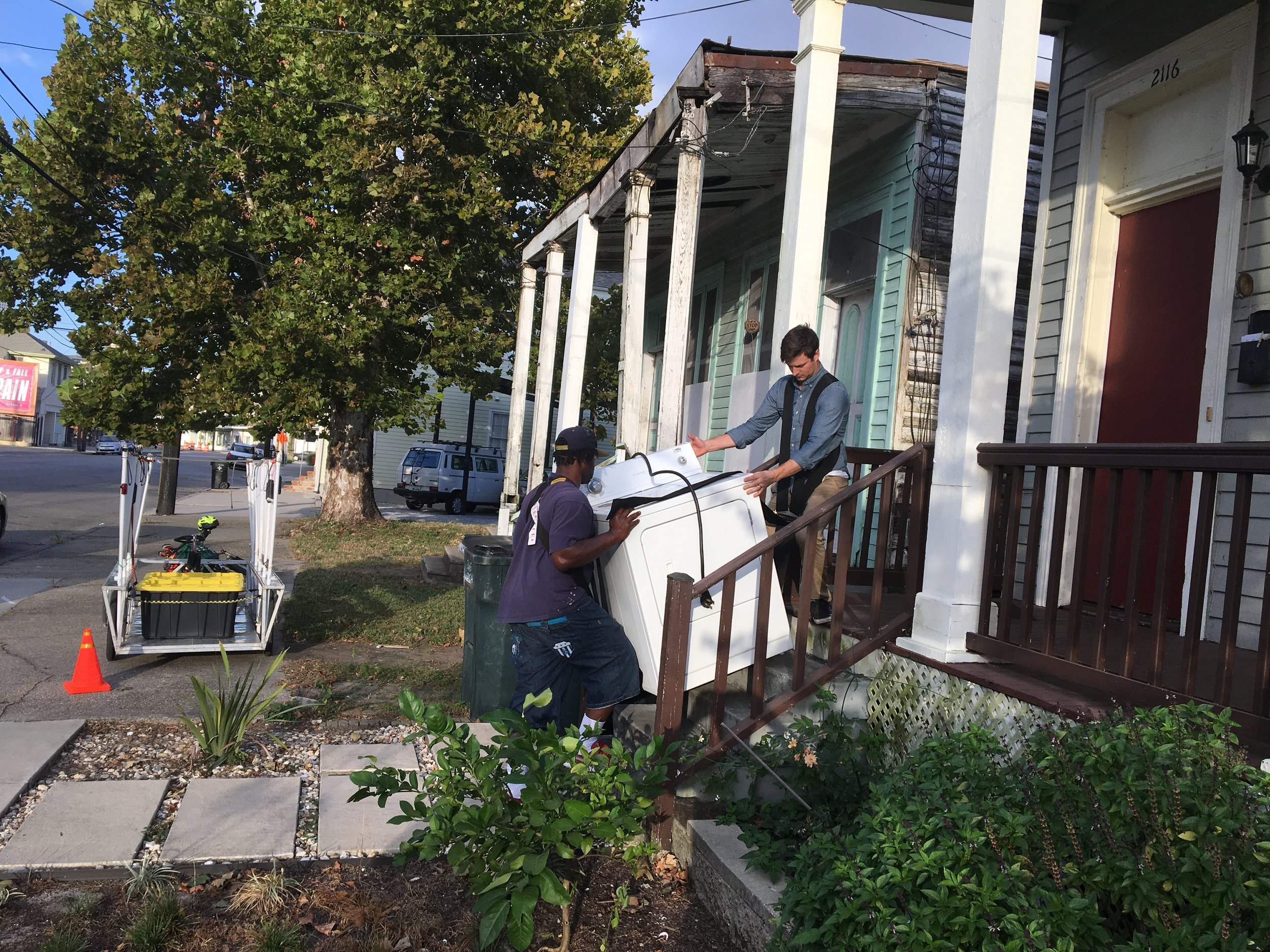 Client's husband and Freddy moving in a dryer.