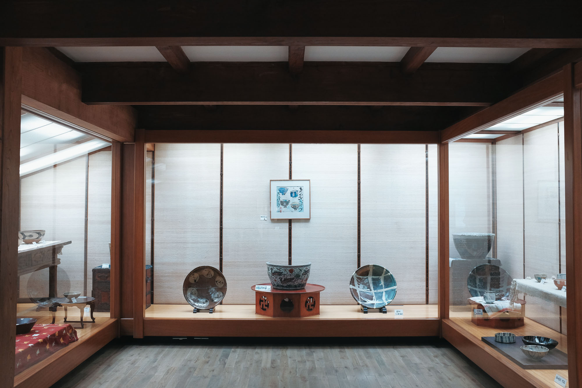 A selection of Hamada's pottery along side furniture pieces from his personal collection.