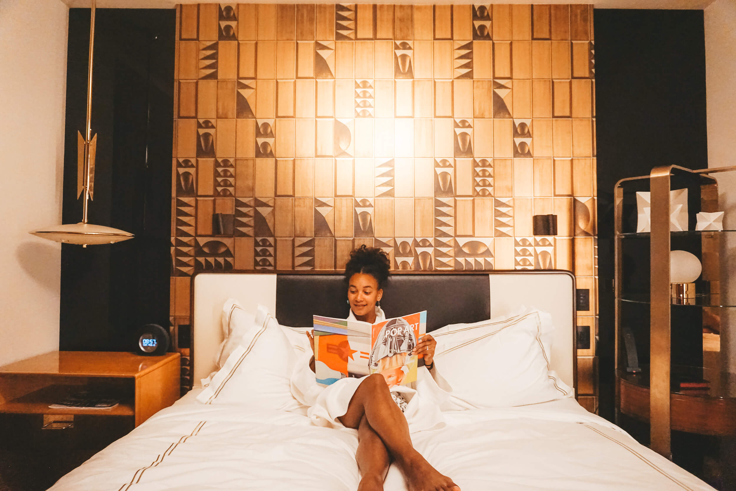 Travel and wellness blogger reading in hotel bed.