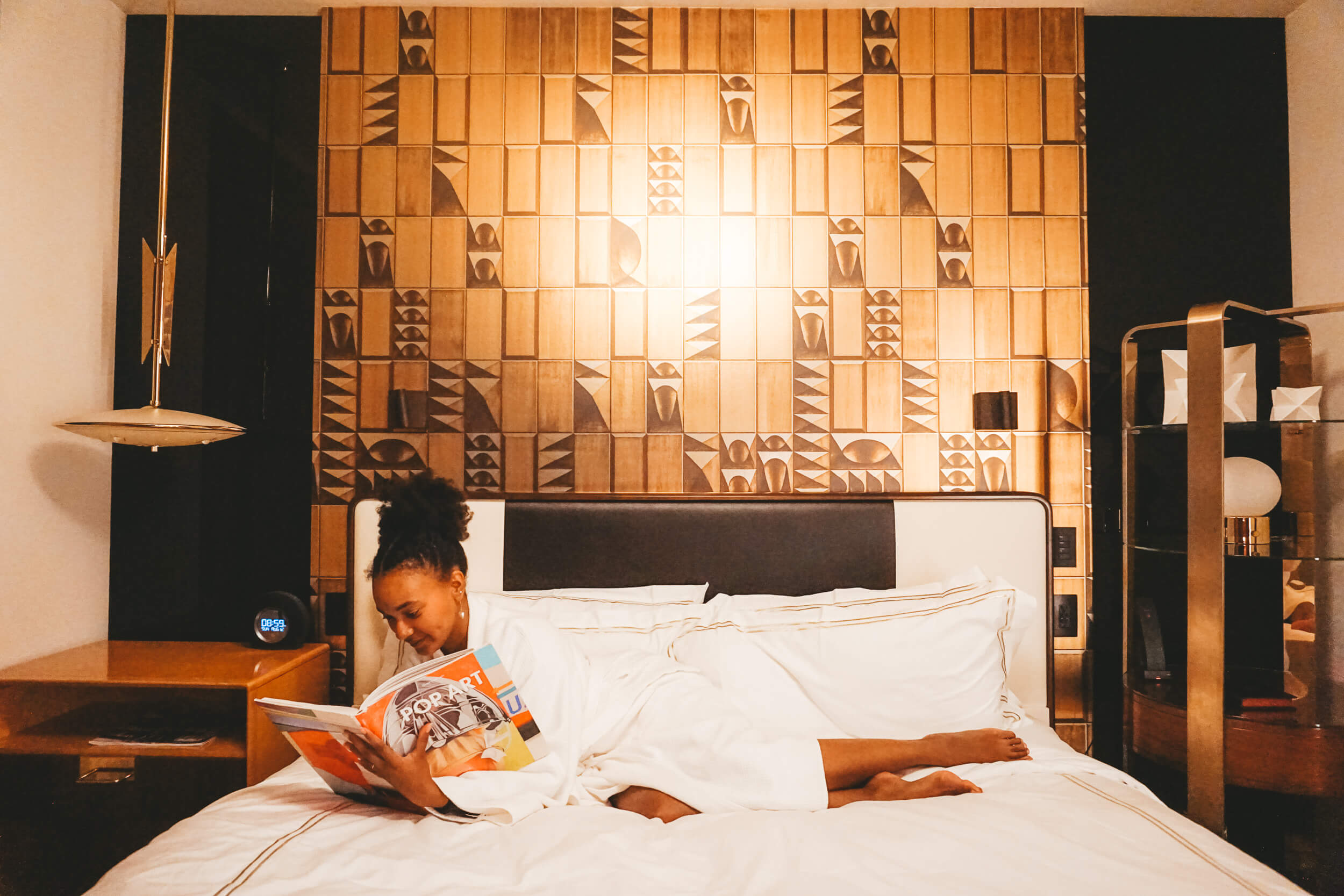 WOC traveler reading in bed at the Viceroy Chicago