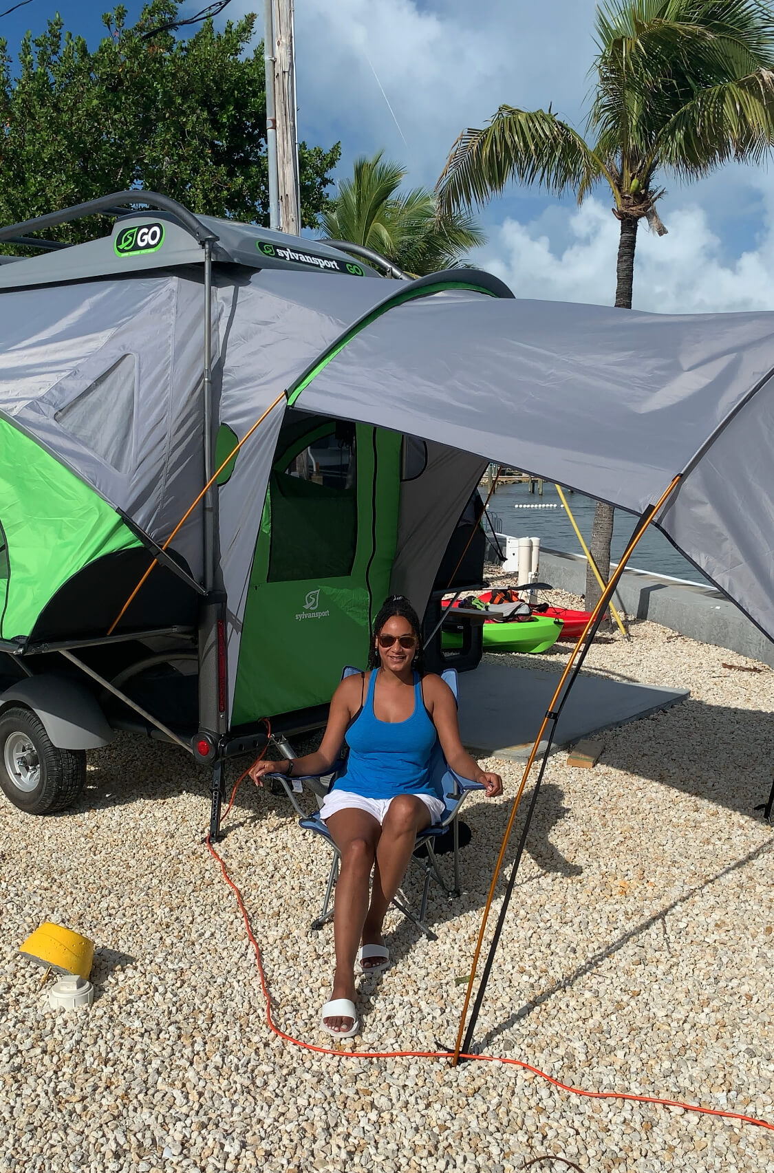 Black woman camping with pop up tent trailer - ochristine
